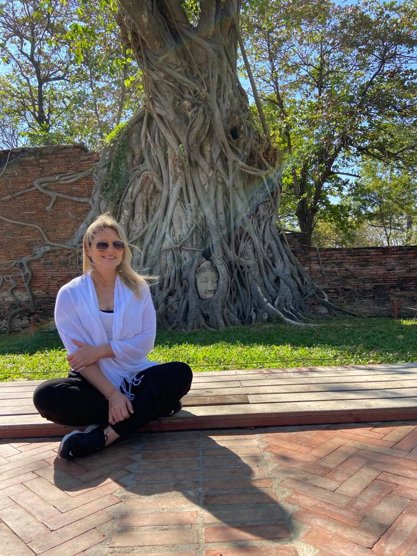 Image of the author, Lynn Howard, sitting under a banyan tree with a buddha's head in the roots.